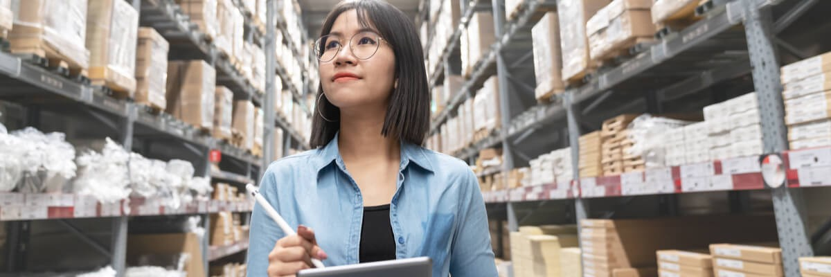 Young  woman  looking up stocktaking inventory in warehouse store by computer tablet