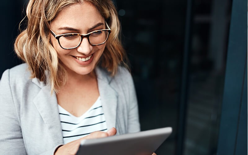 Smiling business woman on tablet outside